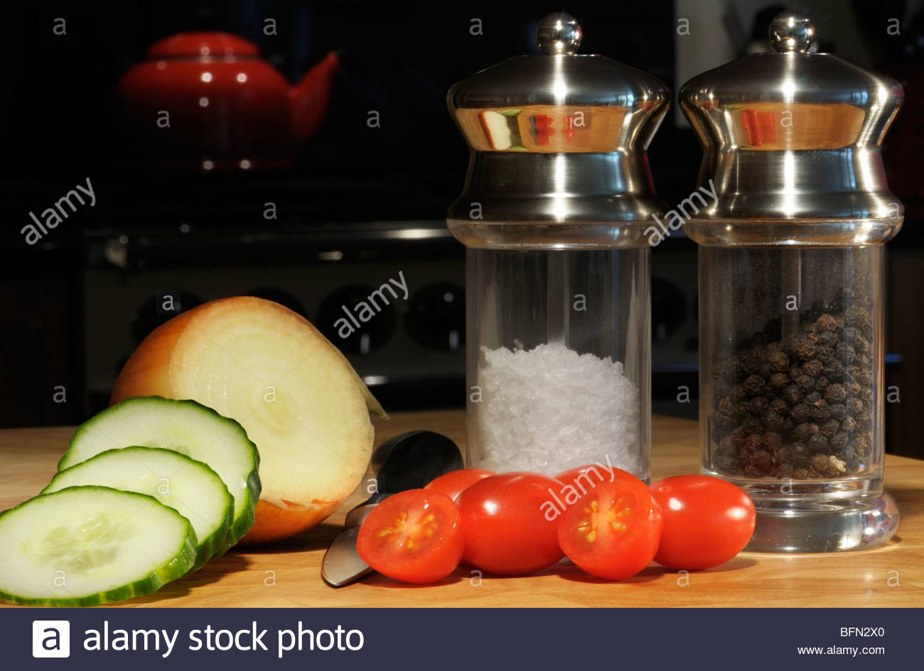 Straight on image of cucumber, onion and tomatoes with salt and pepper mills on a chopping board, Dorset, England, - Stock Image