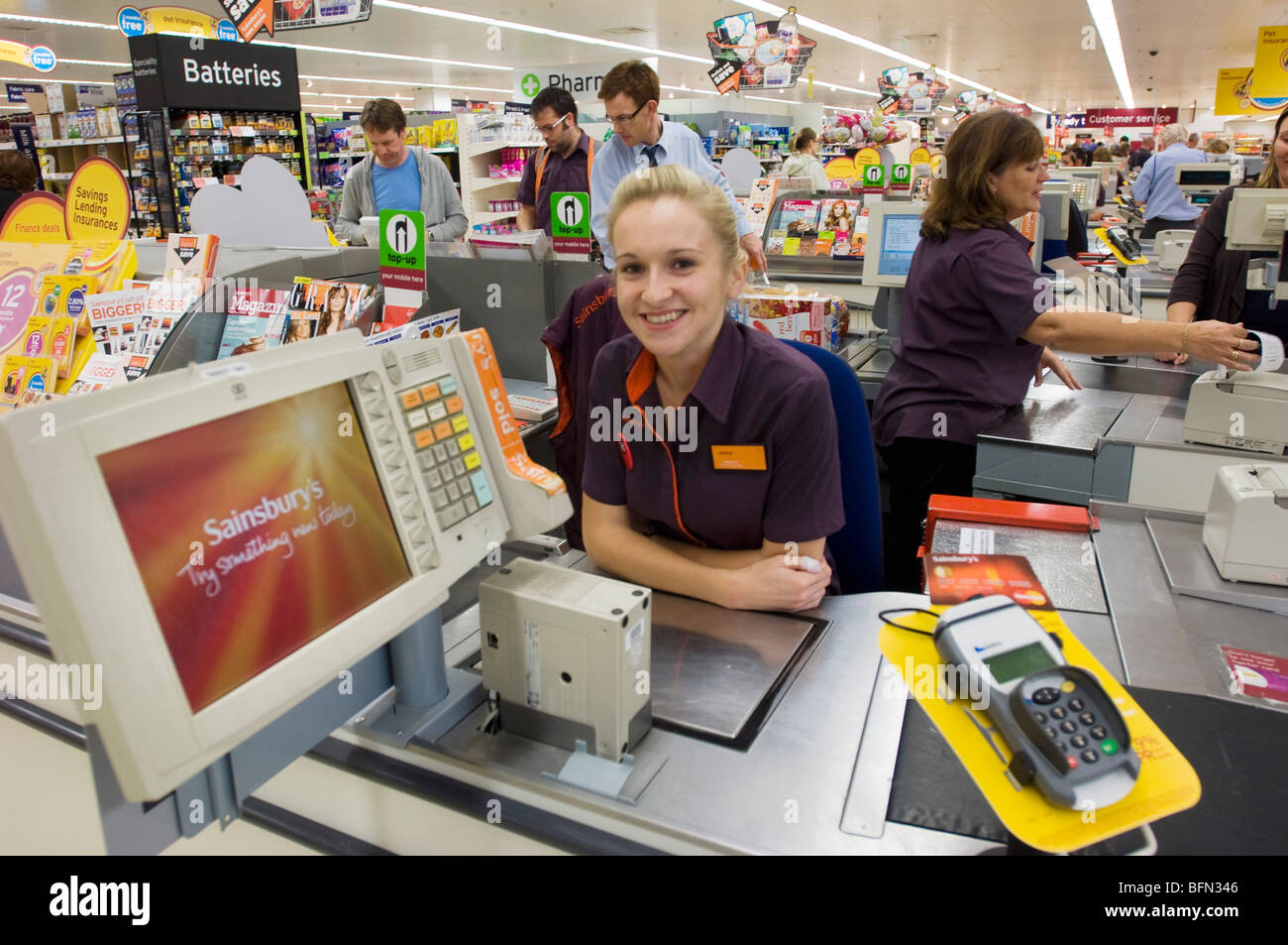 Sainsbury's supermarket. Smiling blonde girl in uniform at a checkout desk - Stock Image