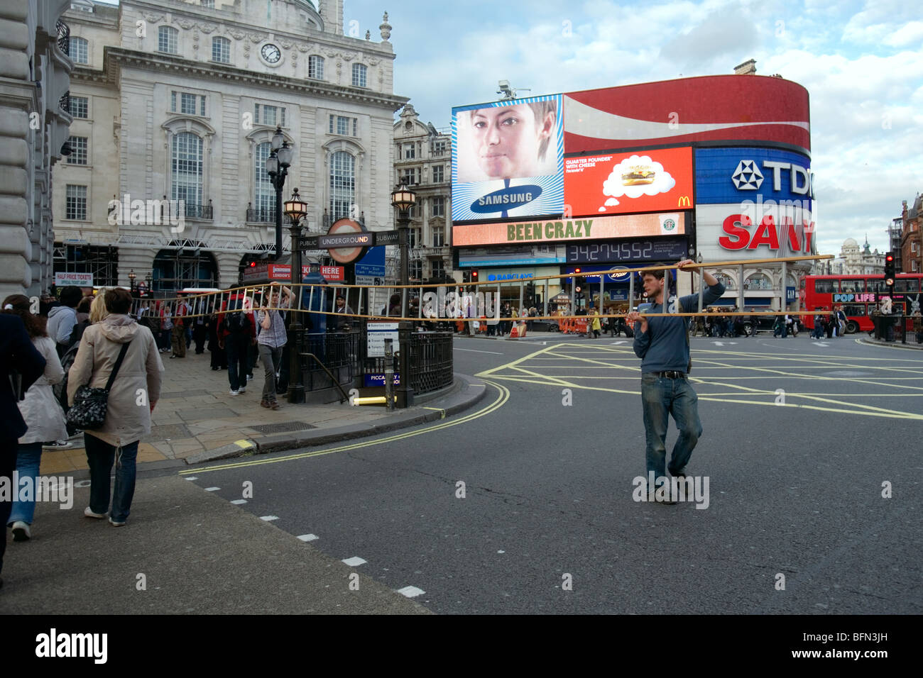 a man with a long ladder crosses the street at picadilly in london - Stock Image