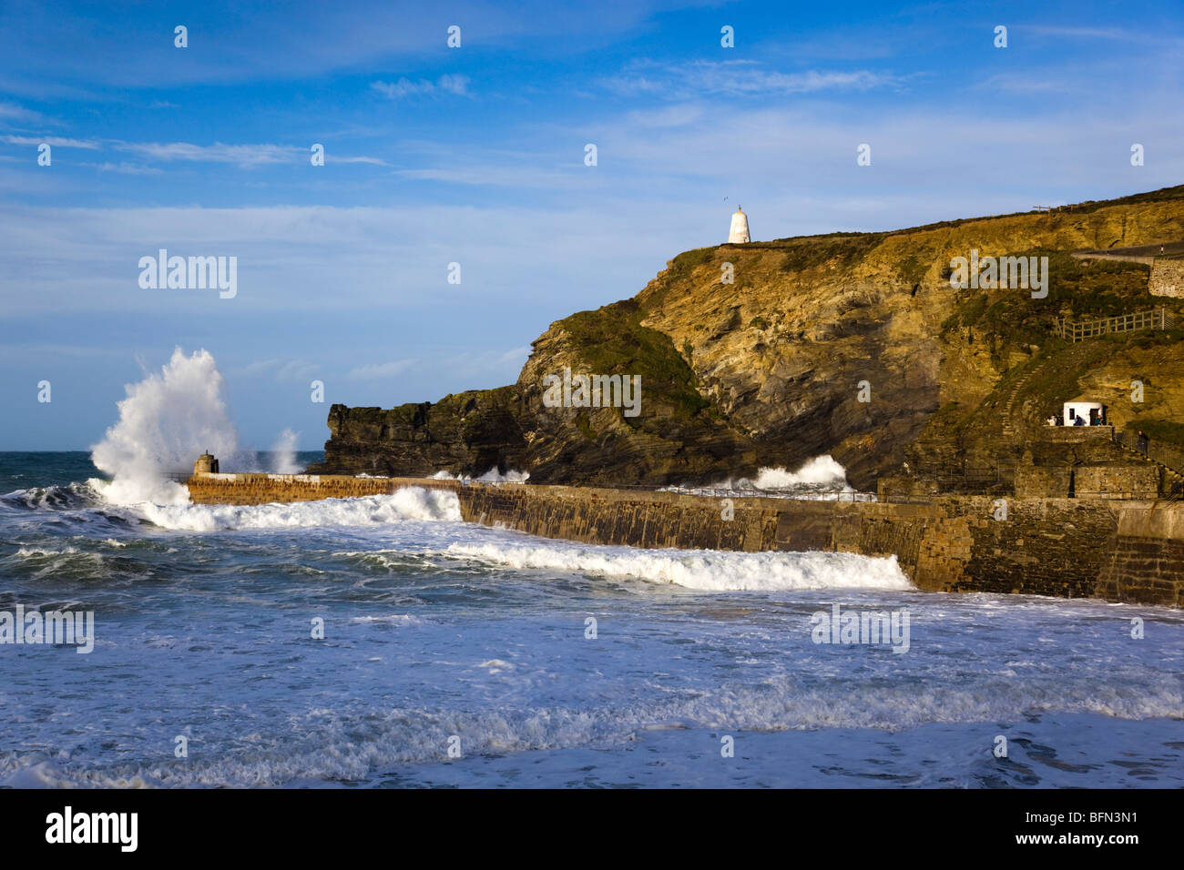 Portreath; waves break over the pier in a storm; Cornwall - Stock Image