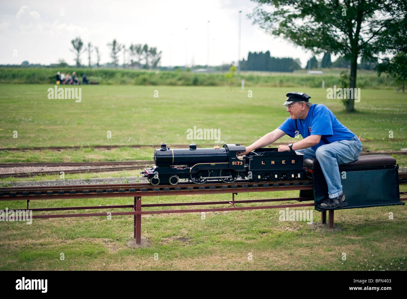 Miniature railway enthusiast rides a miniature train in Canvey Island, Essex. - Stock Image