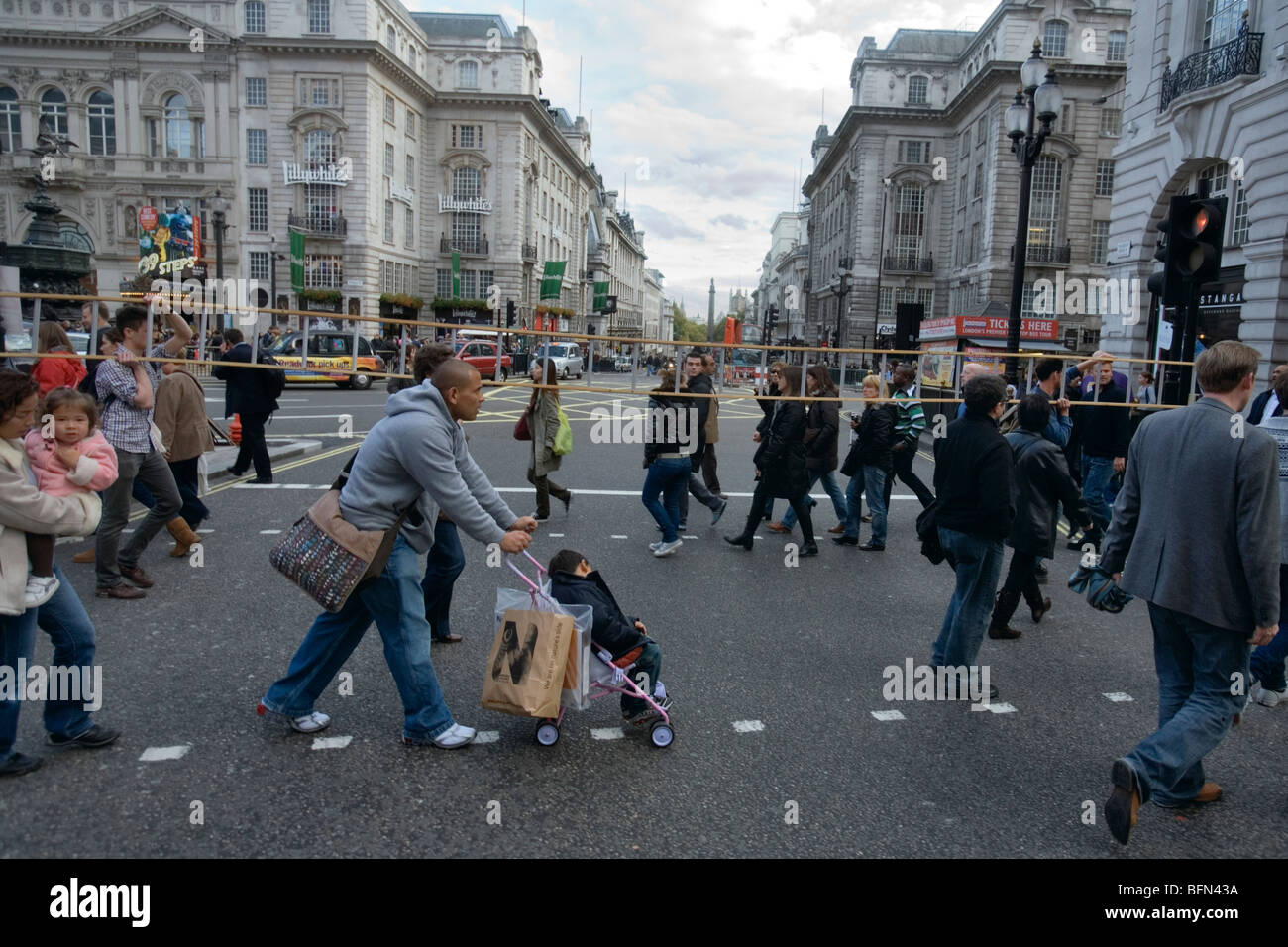 a man with a long ladder crosses the street at piccadilly circus in london - Stock Image