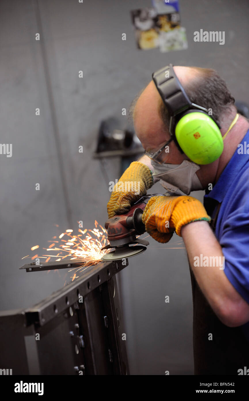 Manufacturing: a metal worker uses an angle grinder in a metal fabrication factory in Brighton. - Stock Image