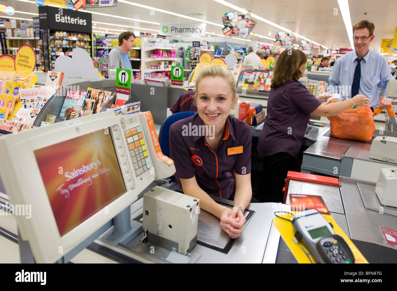 Sainsbury's supermarket. Smiling girl in uniform at the till of a checkout desk. - Stock Image
