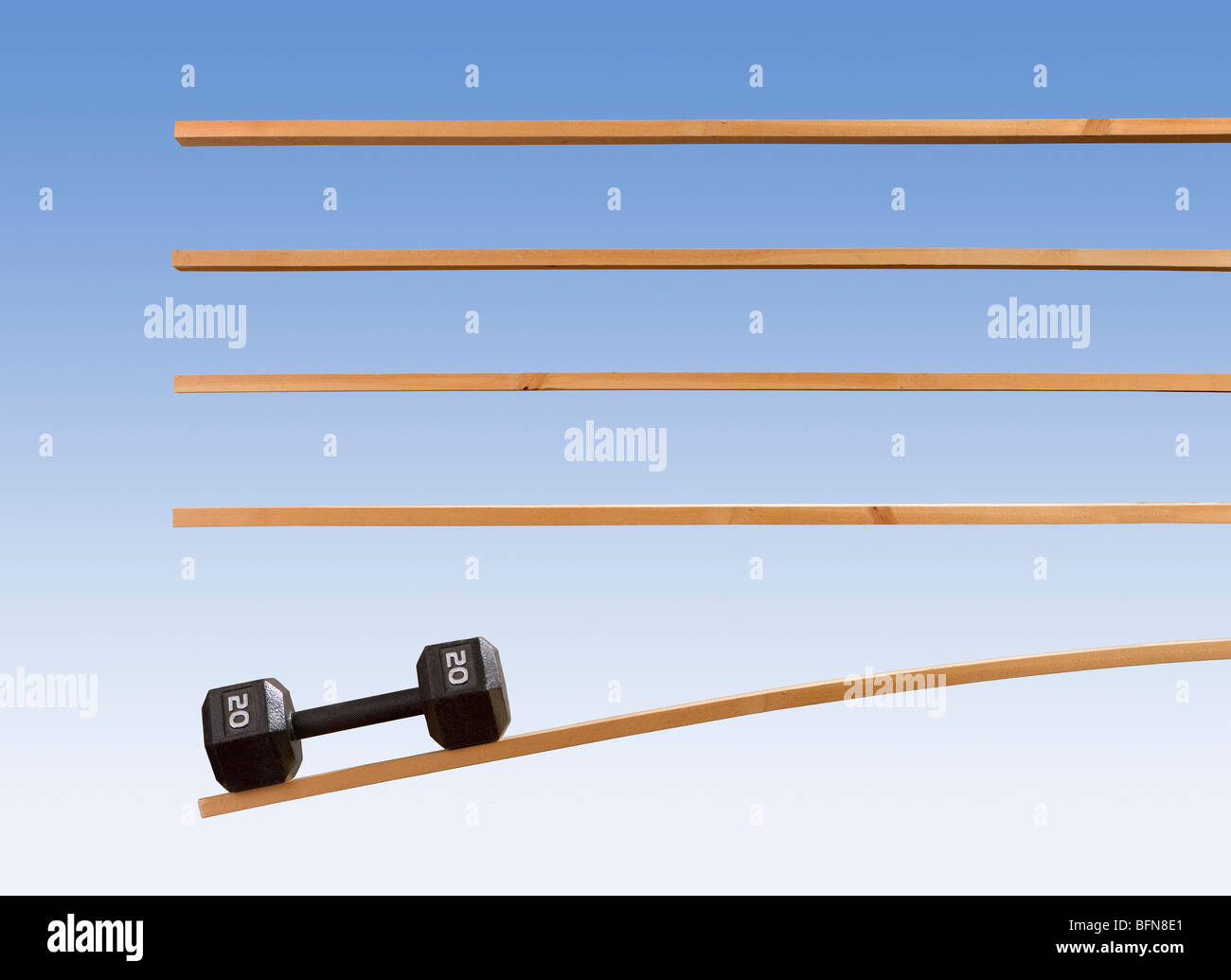 Gravity demonstration using strips of wood and a 20 pound dumbell or weight. - Stock Image