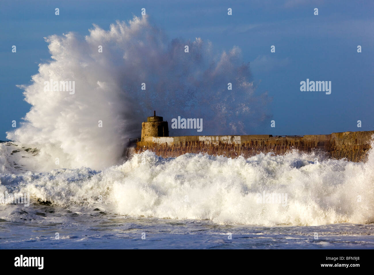 Portreath; wave breaks over the pier in a storm; Cornwall - Stock Image