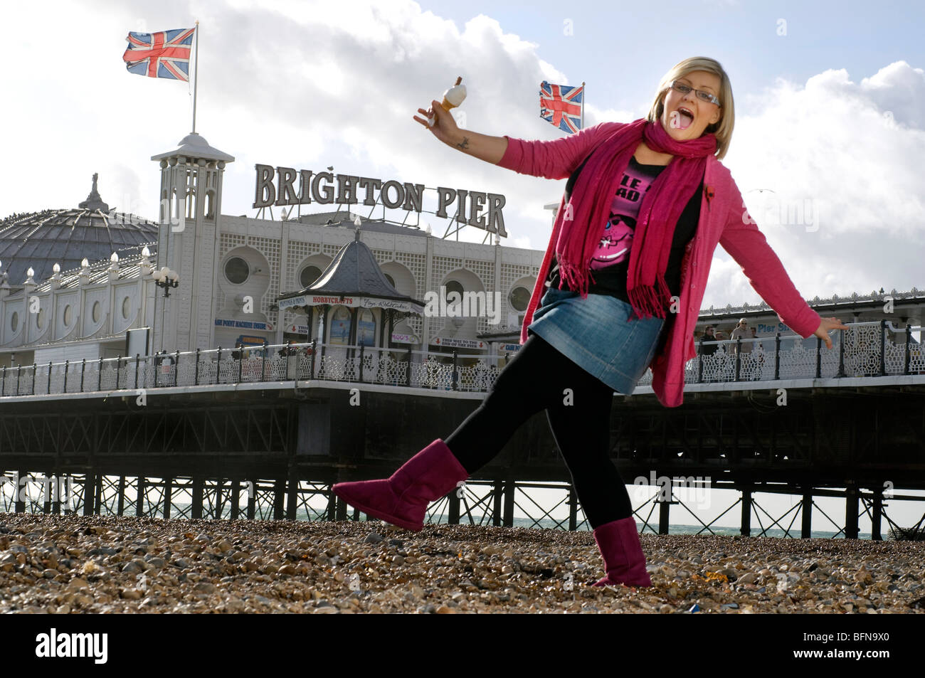 Girl with ice cream cone in front of Brighton pier. - Stock Image