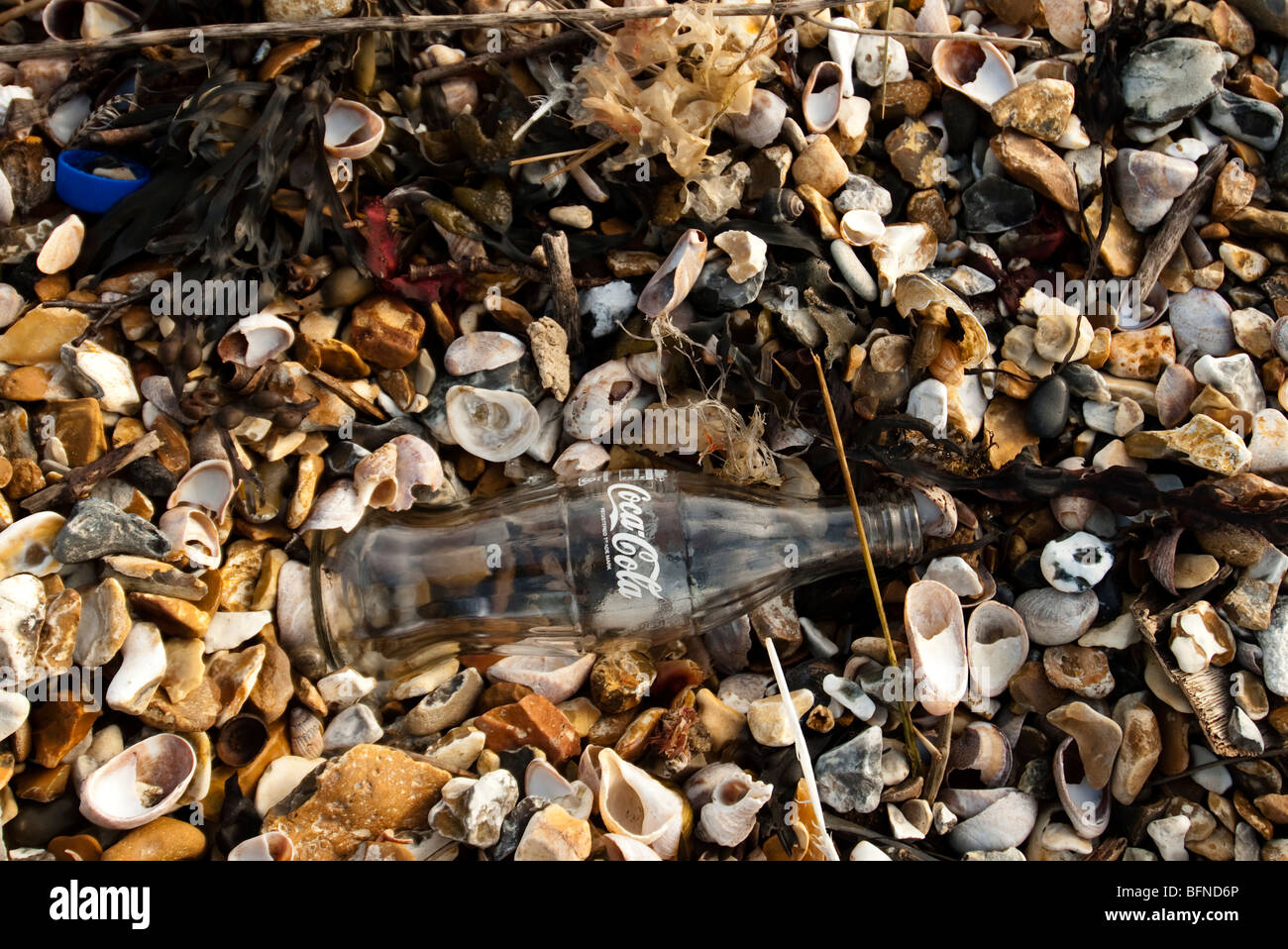 coca cola bottle swept up on the beach Stock Photo