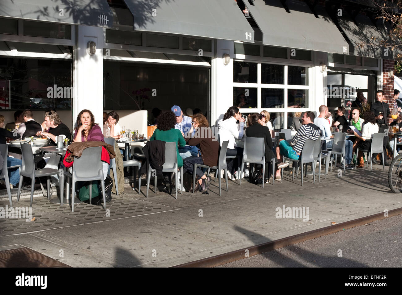 varied group New Yorkers eating Sunday brunch at outdoor tables seating at Ninth Avenue sidewalk cafe in Hells Kitchen - Stock Image
