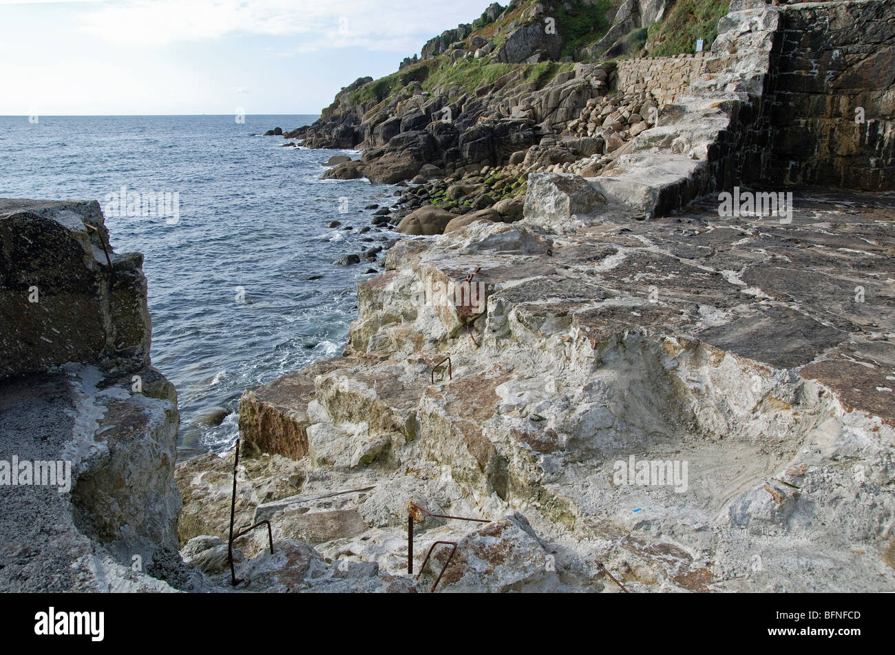 the damaged harbour  wall at lamorna cove in cornwall, uk ,  the damage has occured during recent high stormy seas - Stock Image