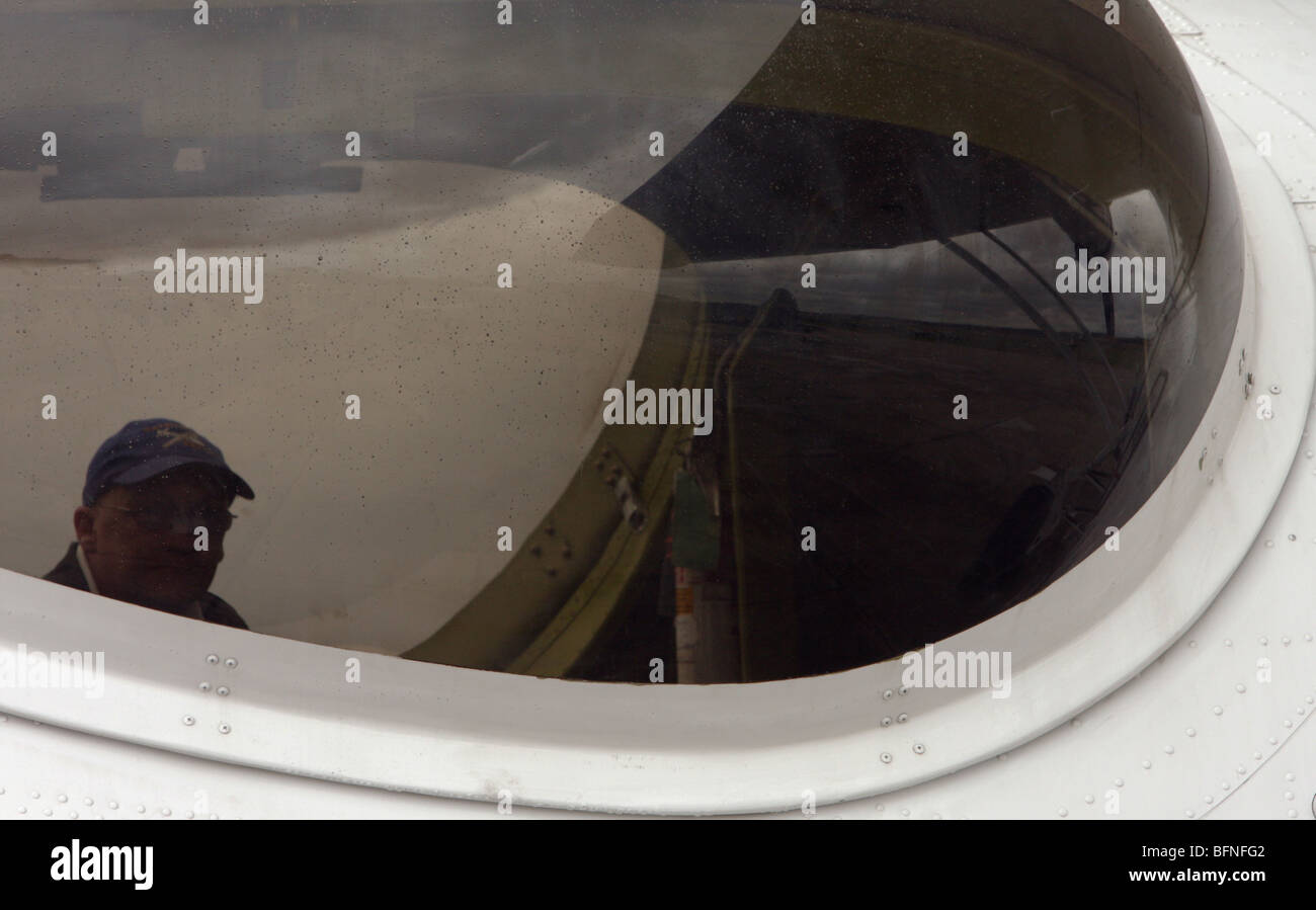 A man sitting an a PBY Catalina looks out of the blister window. - Stock Image