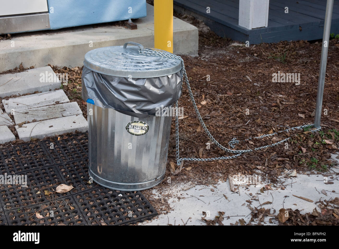 garbage can chained as anti-theft deterrant at outdoor location, North Florida - Stock Image