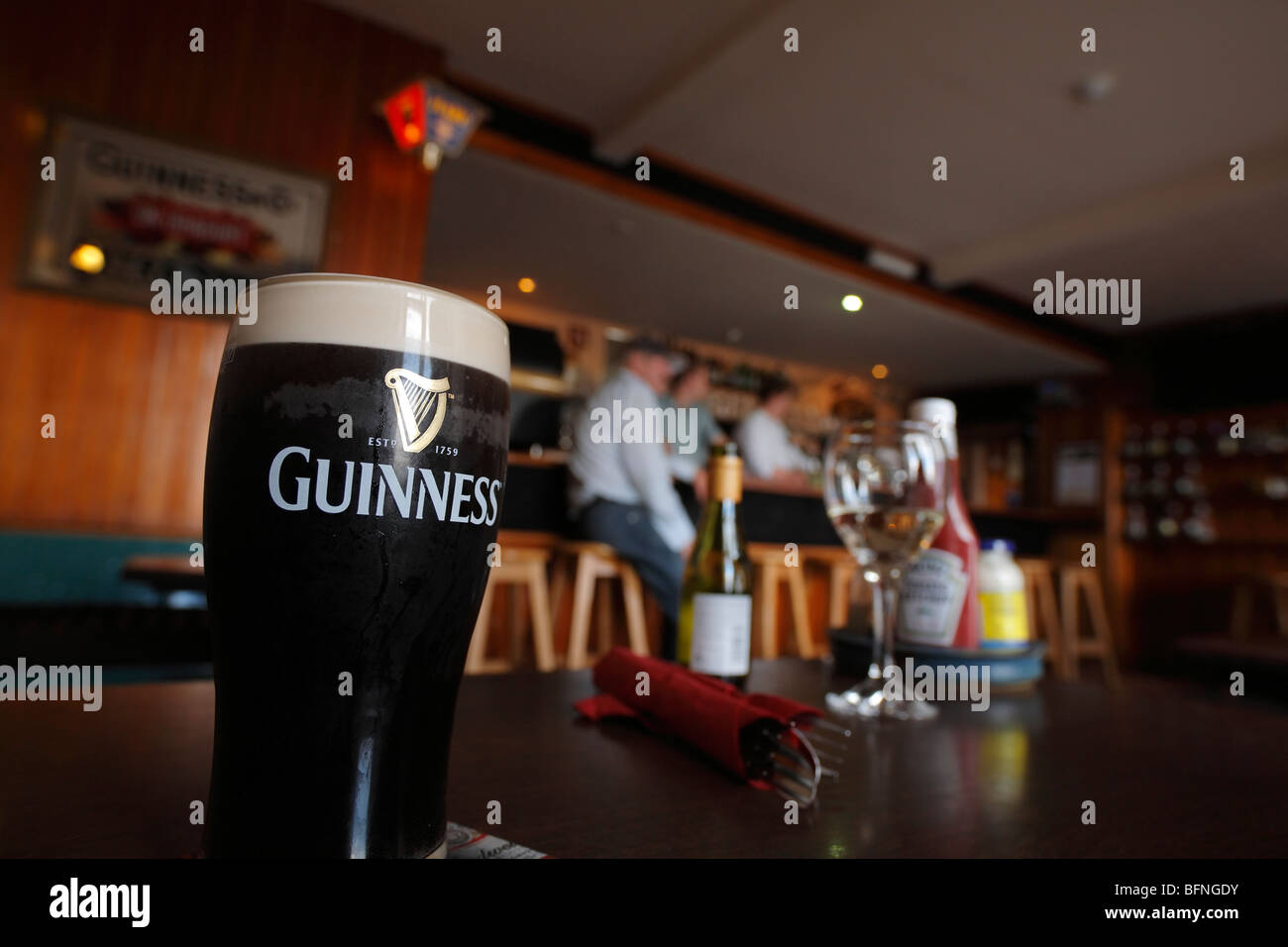 a pint of Guinness on a table in the Roundstone House a bar and hotel in Roundstone, Connemara, Ireland - Stock Image