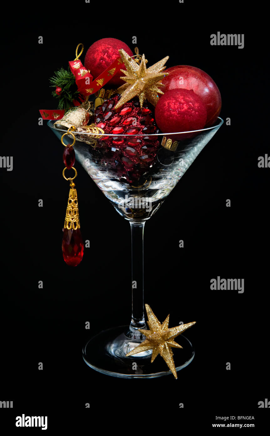 Red and gold christmas decorations in cocktail glass against a black background - Stock Image
