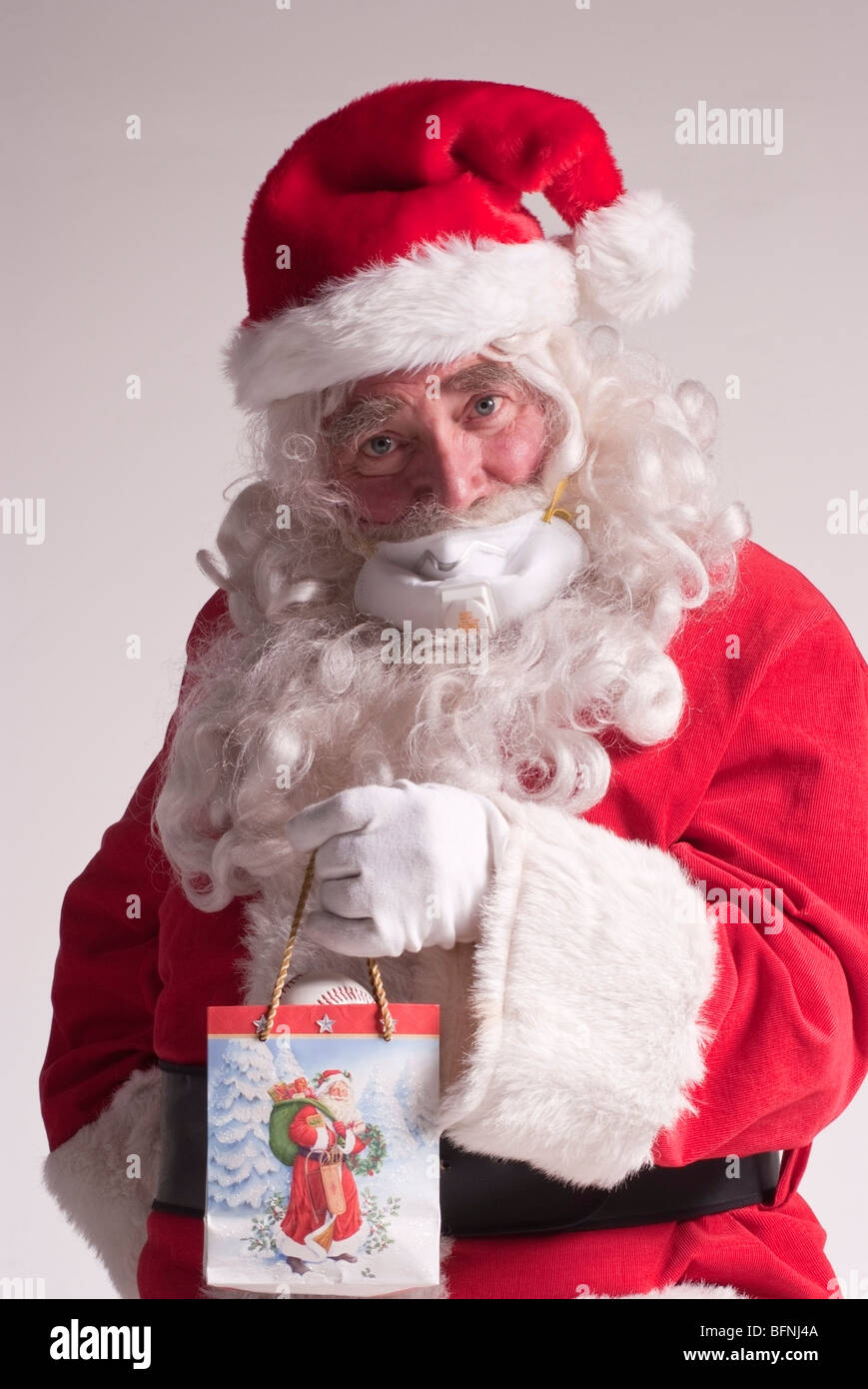 65-year-old man dressed as Santa Claus for Christmas wearing a breathing mask to protect against the H1N1 virus - Stock Image