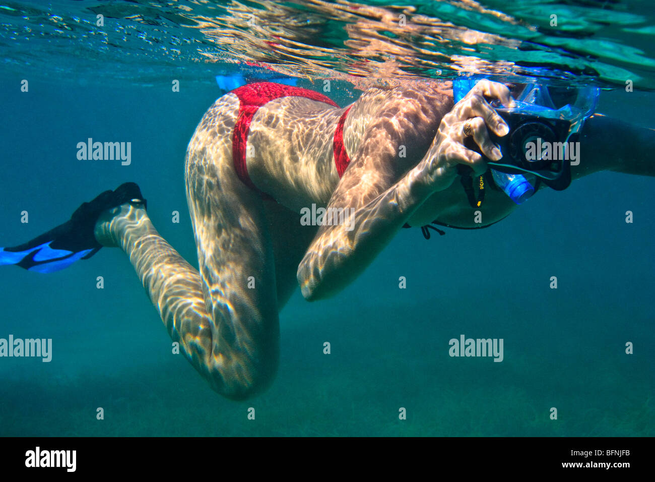 Young woman snorkeling and taking pictures underwater Stock Photo