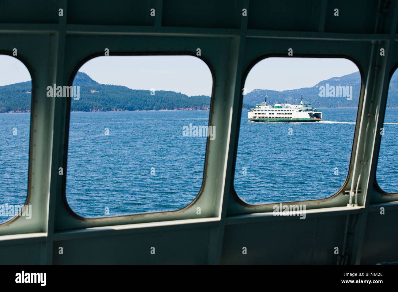 A Washington State ferry seen through the windows of another stste ferry in the San Juan Islands, Washington, USA. - Stock Image