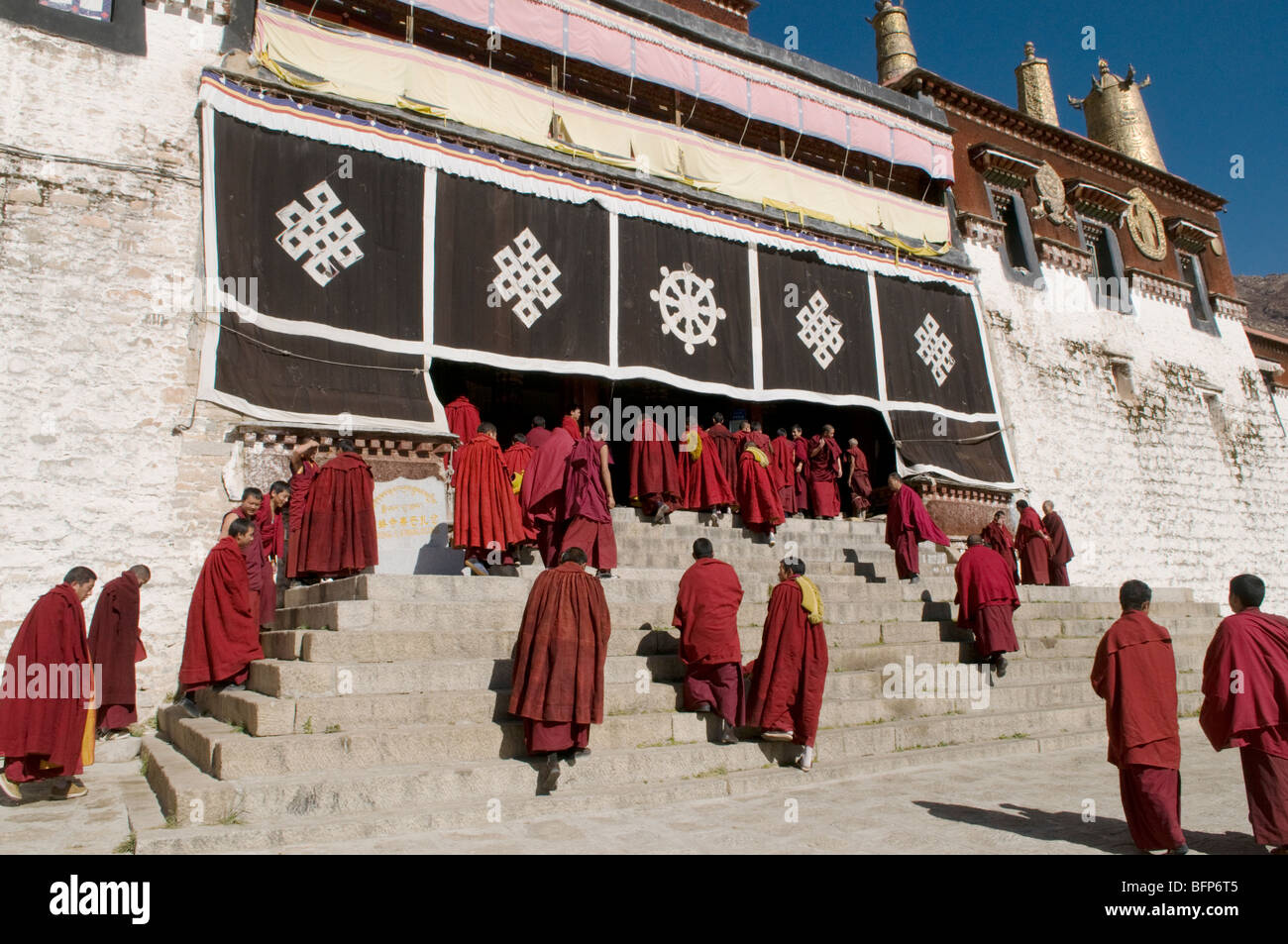 Monks in front of the main prayer hall at the famous Drepung Monastery, the largest in Lhasa Tibet. - Stock Image