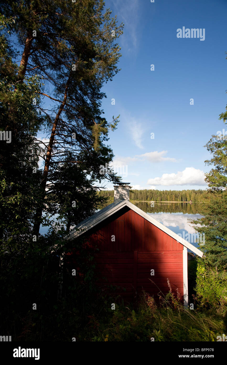 Red cabin by a lake , Finland - Stock Image