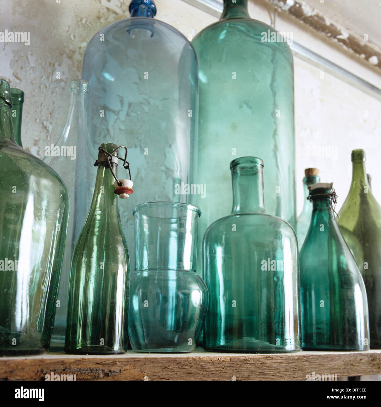 Row of assorted antique bottles and glassware on shelf / ledge Stock Photo