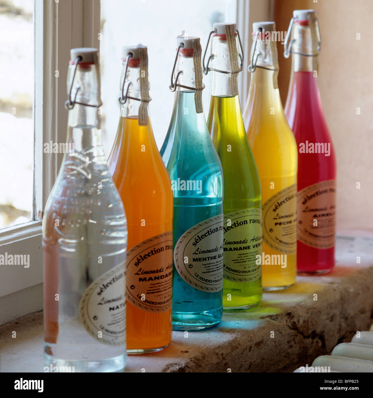 Row of glass bottles filled with multicoloured liquids on windowsill / ledge Stock Photo