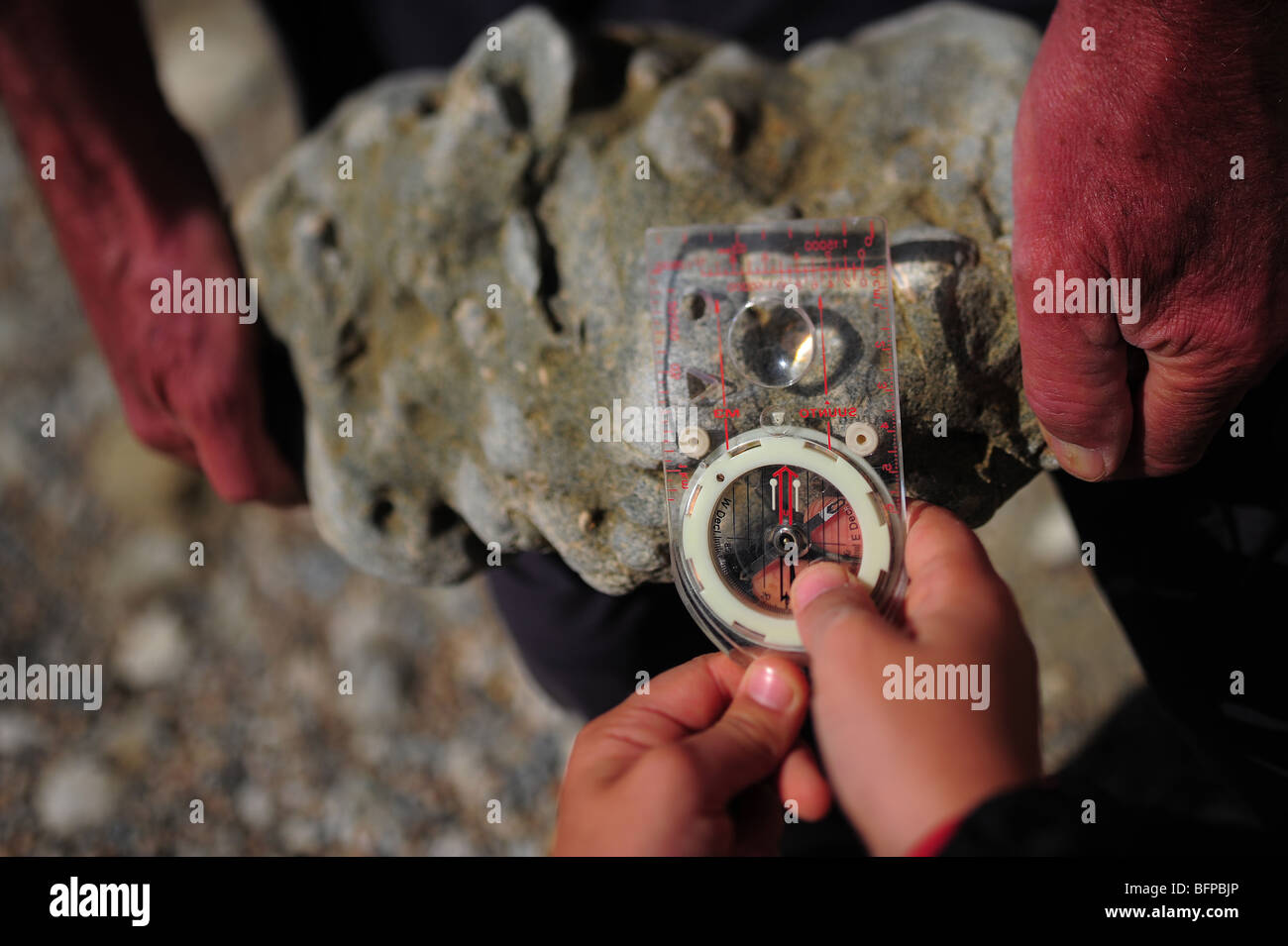 A child learning how to use a magnifying lens while looking for fossils at Lulworth Cove, Dorset, UK - Stock Image