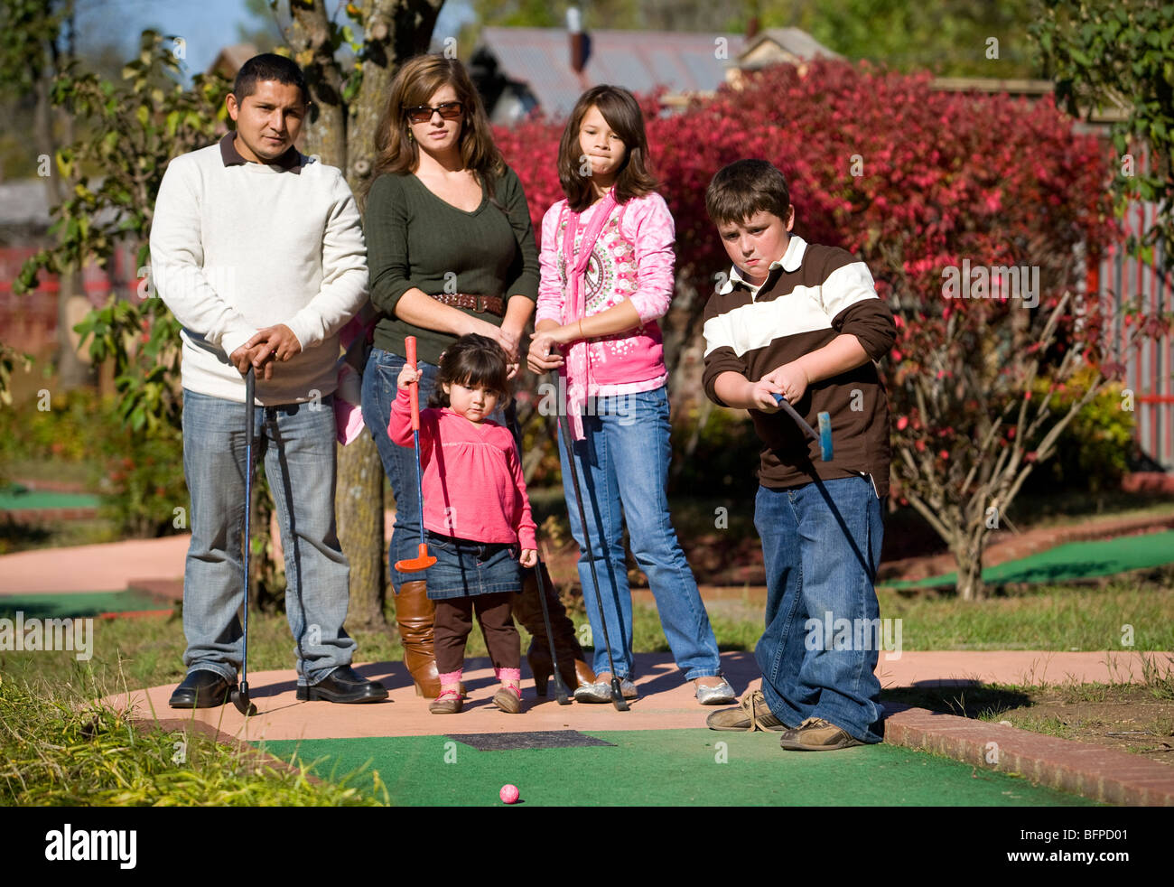 A mixed-race family participates in a round of miniature golf. Stock Photo