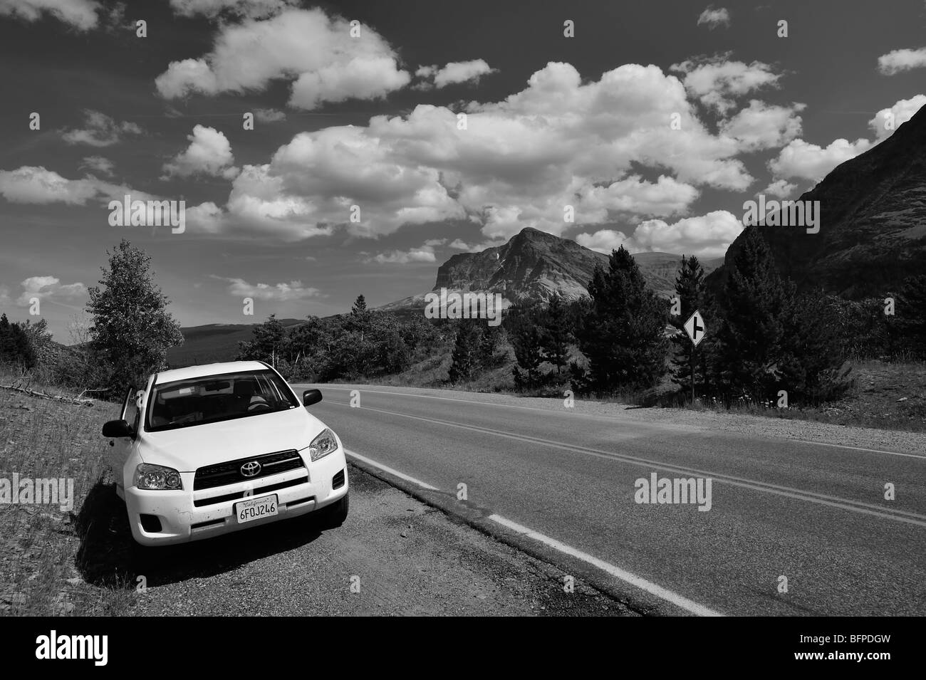 White car parked on the road next to the Sherburne lake in Many Glaciers area of the Glacier national park, Montana - Stock Image