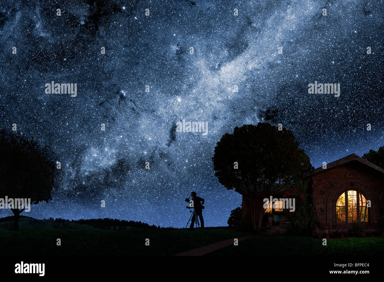 A man gazes at the Milky Way outside his house at night - Stock Image