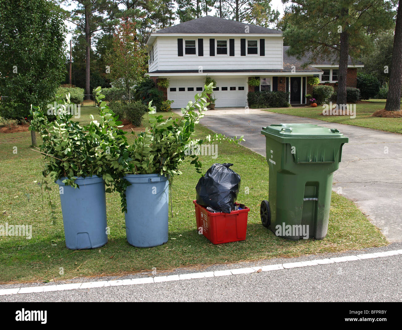 garbage can recycling bin trash yard clippings branches in front of white split-level house in suburban neighborhood - Stock Image