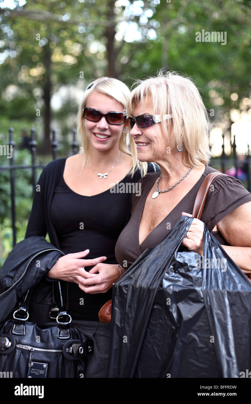 smiling blond Nordic tanned mother & daughter tourists wearing low cut tops Lower Broadway outside City Hall - Stock Image