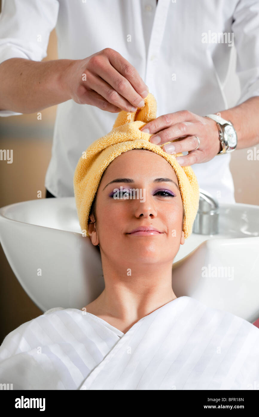 portrait of young woman in hair salon - Stock Image