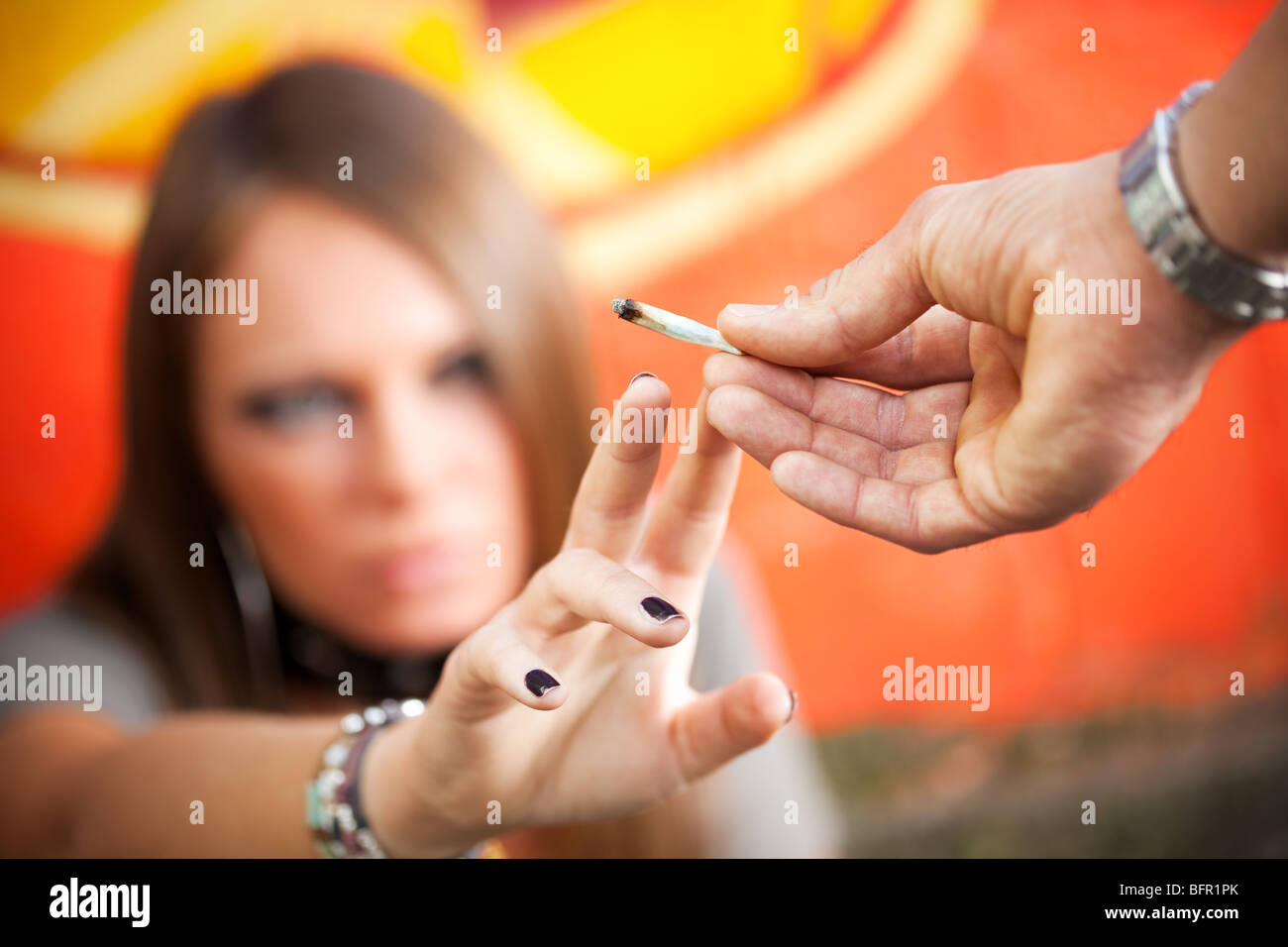 cropped view of two young adults smoking a joint - Stock Image