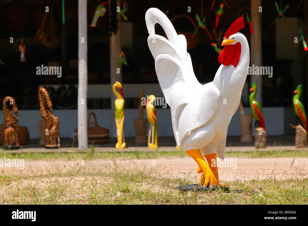 A roadside curios stall with a large carved wooden cockerel and other birds - Stock Image