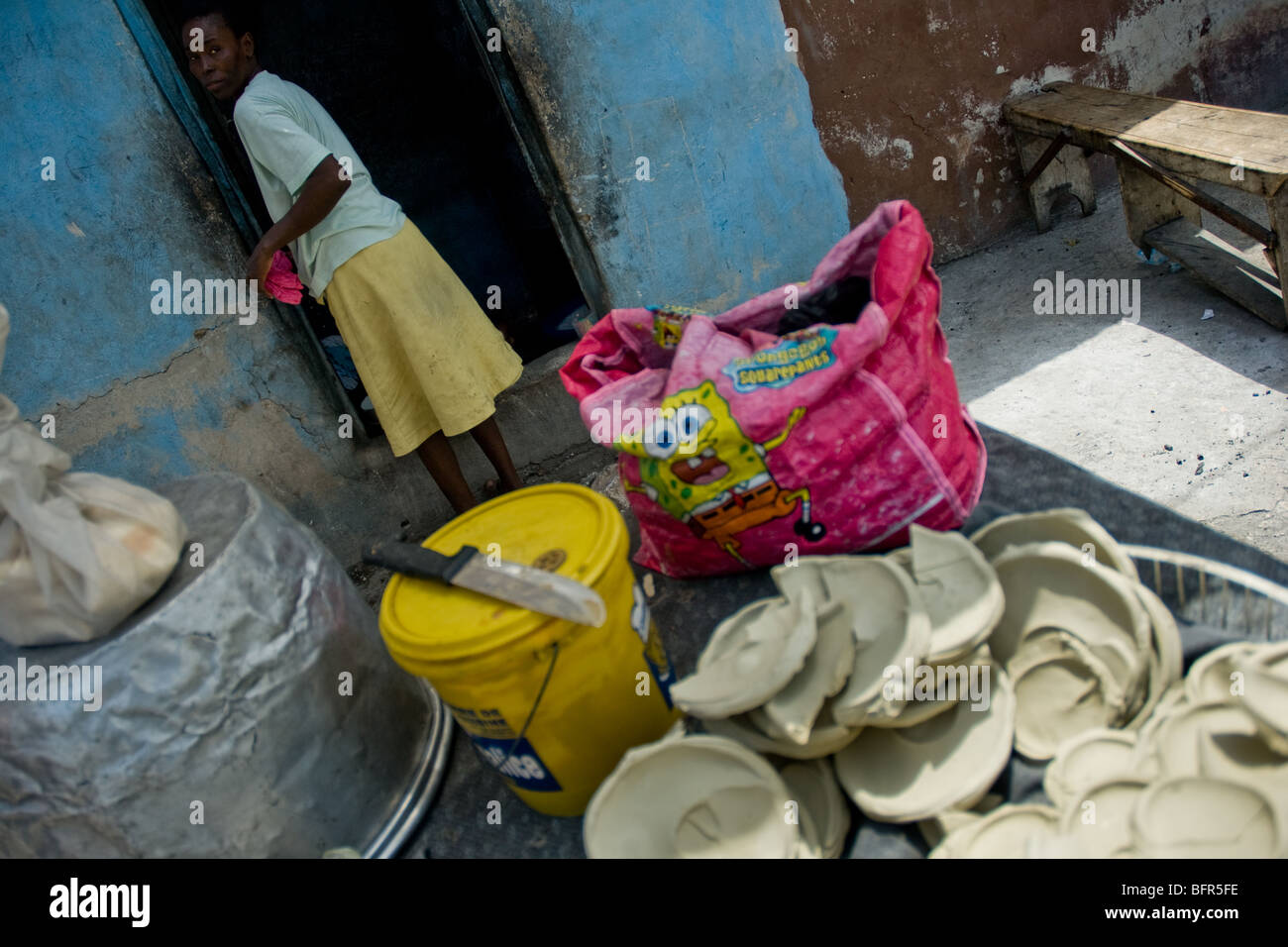 A woman selling dried cakes made from a mixture of yellow dirt, water and salt in Cite Soleil, Port-au-Prince, Haiti. - Stock Image