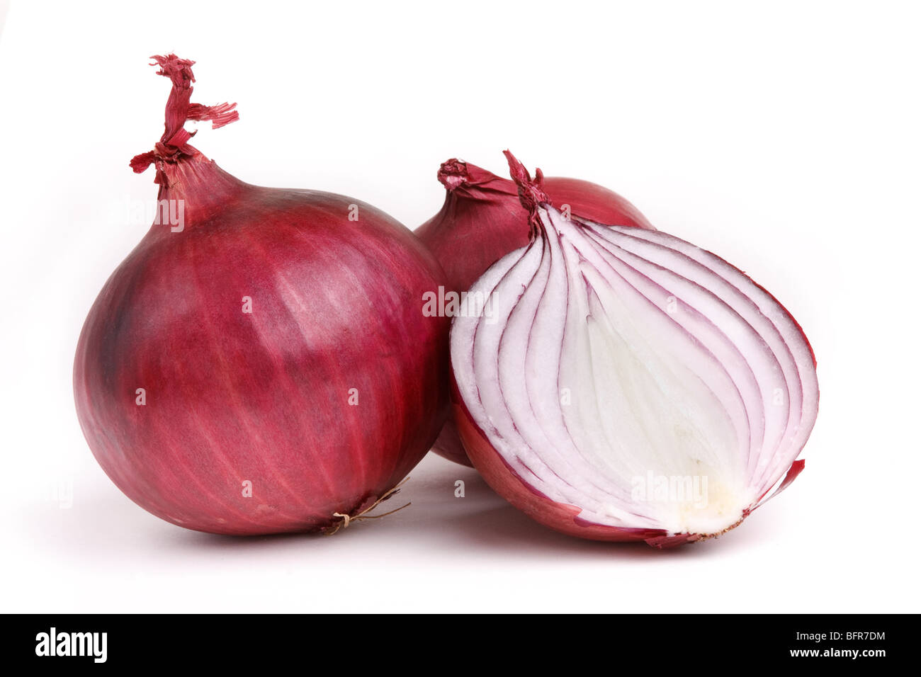 Red onions one sliced against white background. - Stock Image
