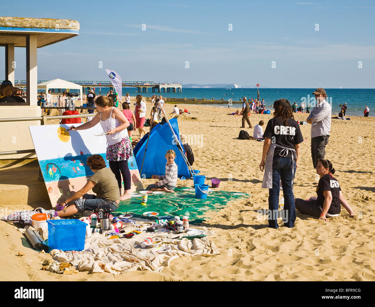 Artists and families painting a mural of the shoreline during the Bournemouth Beach Festival. Dorset. UK. - Stock Image