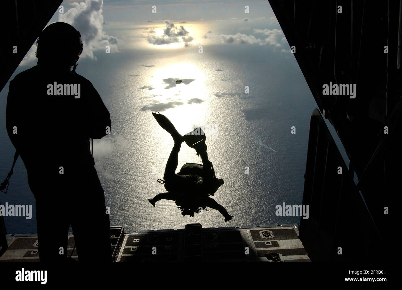 An Air Force pararescueman jumps out of the back of an HC-130 Hercules. - Stock Image