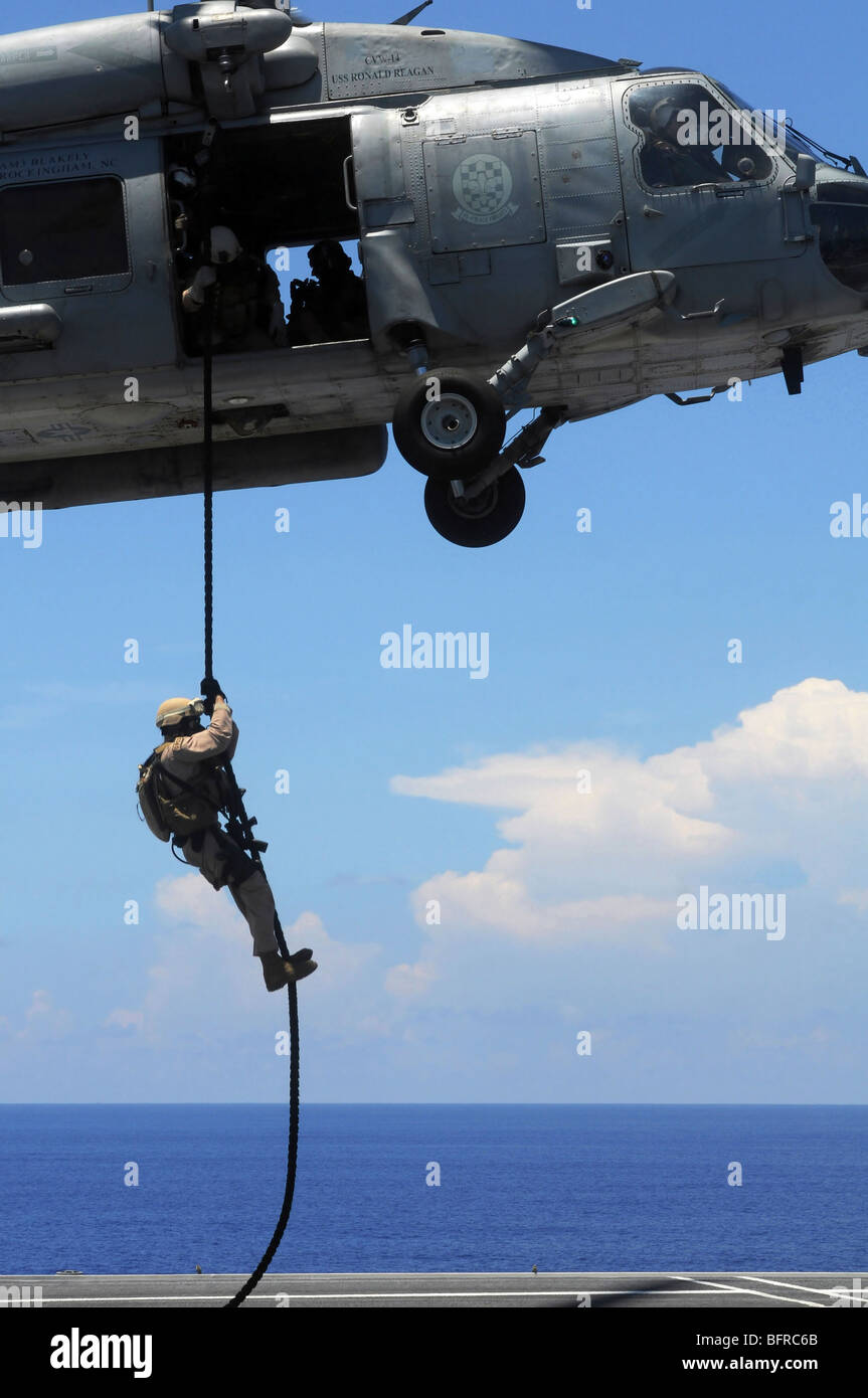 An explosive ordnance disposal technician fast ropes onto the flight deck of the USS Ronald Reagan. - Stock Image
