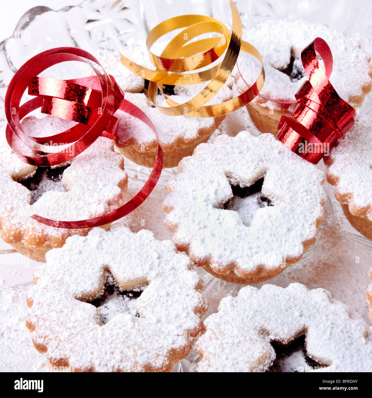 Background image of Sweet Mince Pies and ribbons dusted with icing sugar. - Stock Image