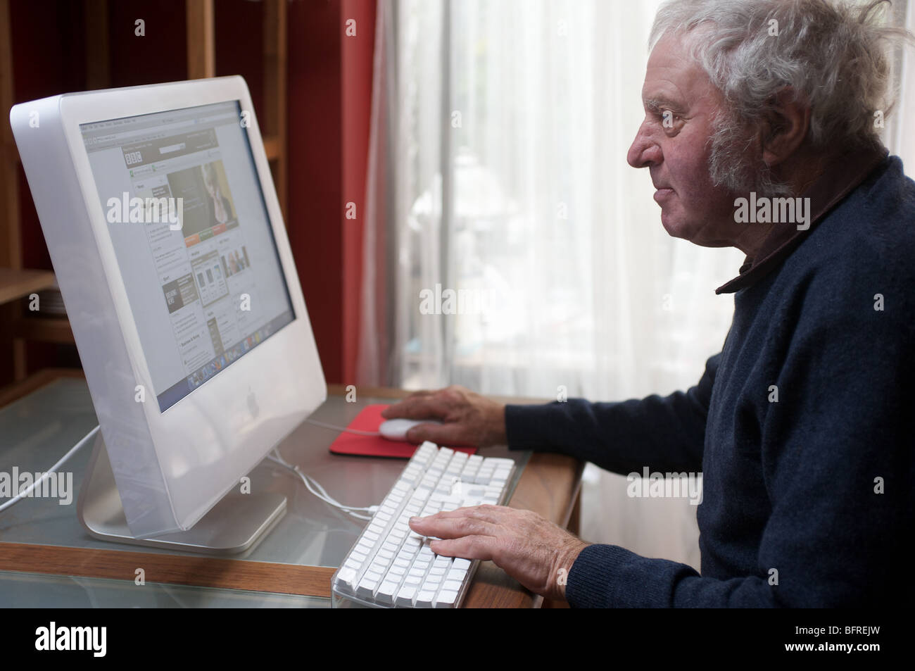 Elderly man at home using a computer to access the internet, Suffolk, UK. - Stock Image