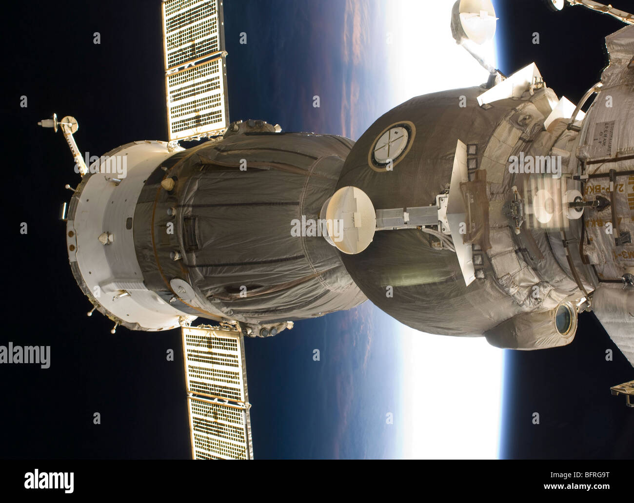 A Soyuz spacecraft backdropped by Earth. - Stock Image