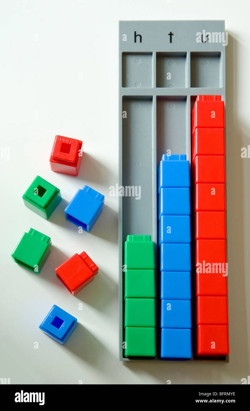 Counting bricks, with a place value tray showing htu (hundreds, tens and units) to help develop young childrens - Stock Image