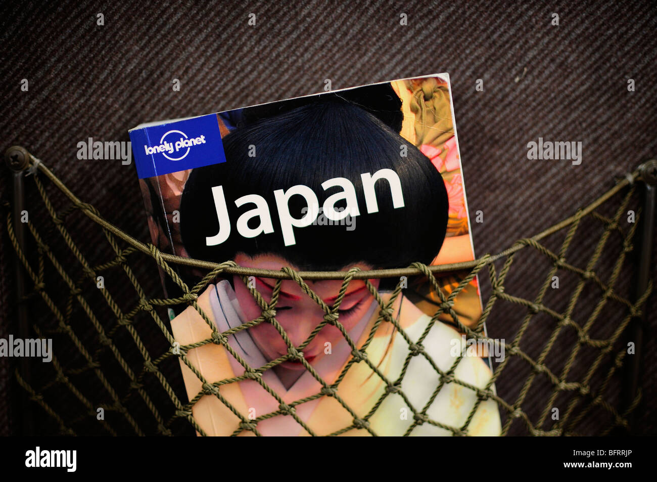 Copy of Lonely Planet Japan travel guide in a train seat pocket, Japan - Stock Image