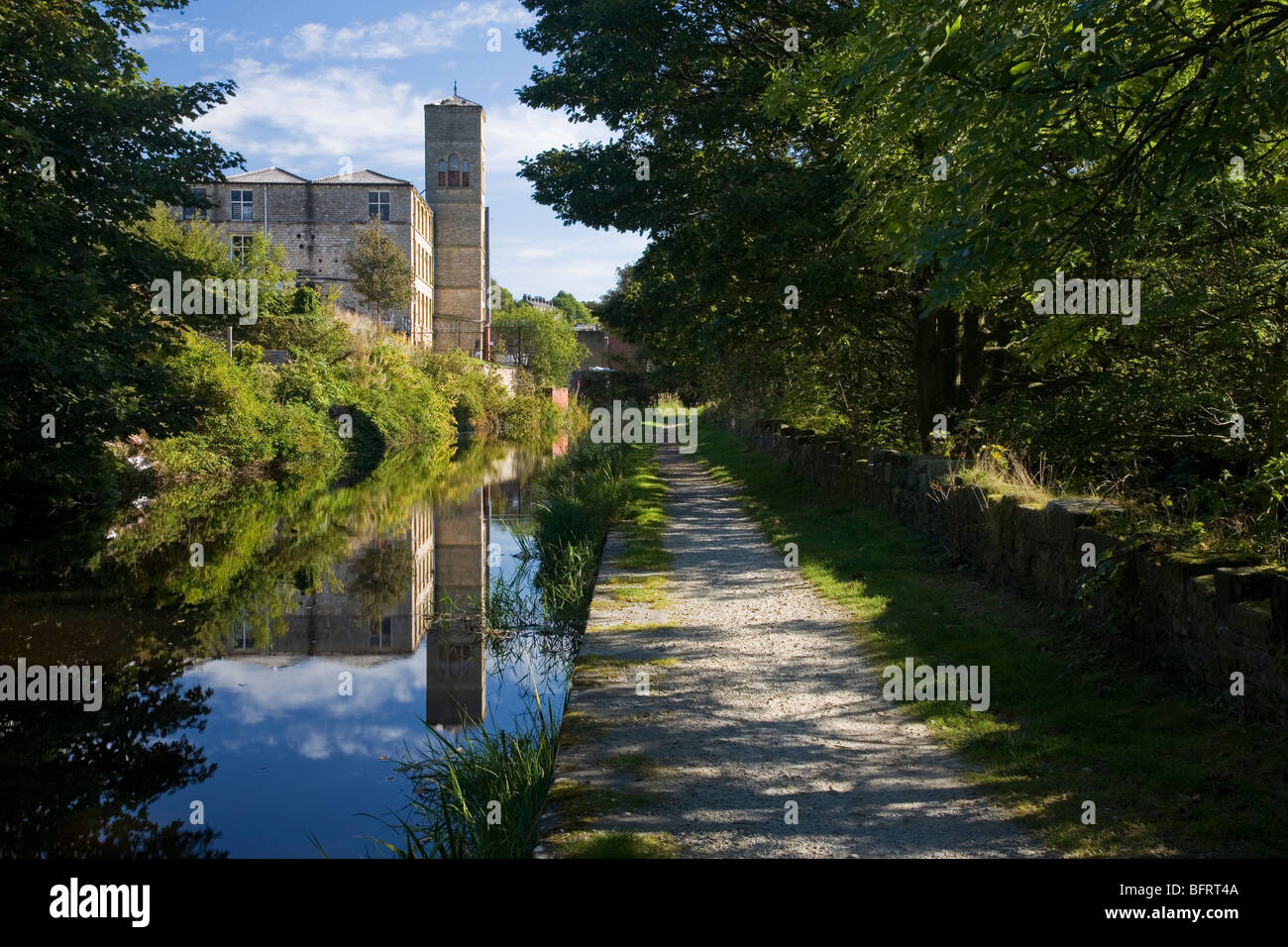The Huddersfield Narrow Canal and old Mill building at Slaithwaite in the Colne Valley, Huddersfield, West Yorkshire, - Stock Image