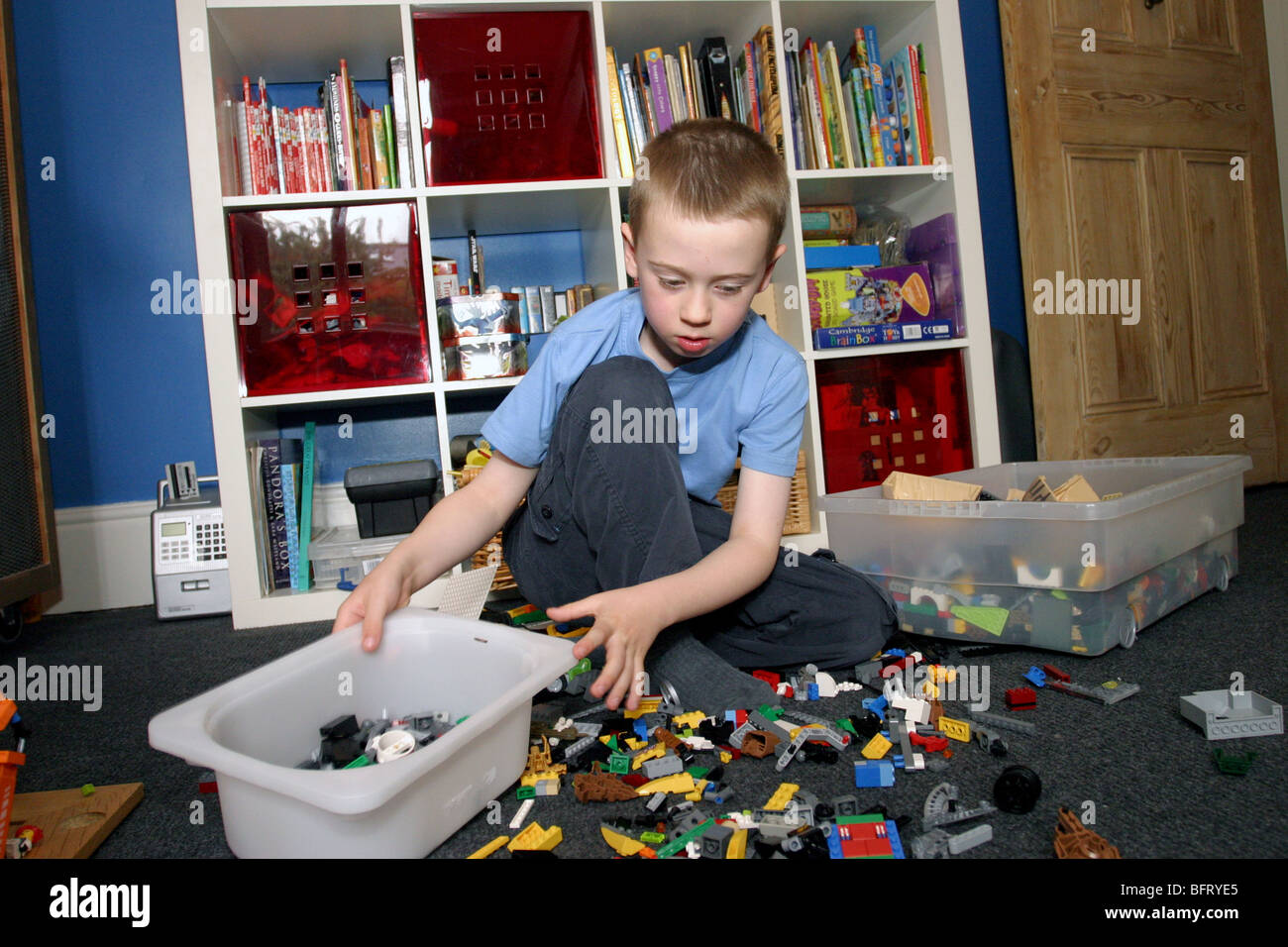 Young Boy Tidying Toys In His Bedroom Stock Photo