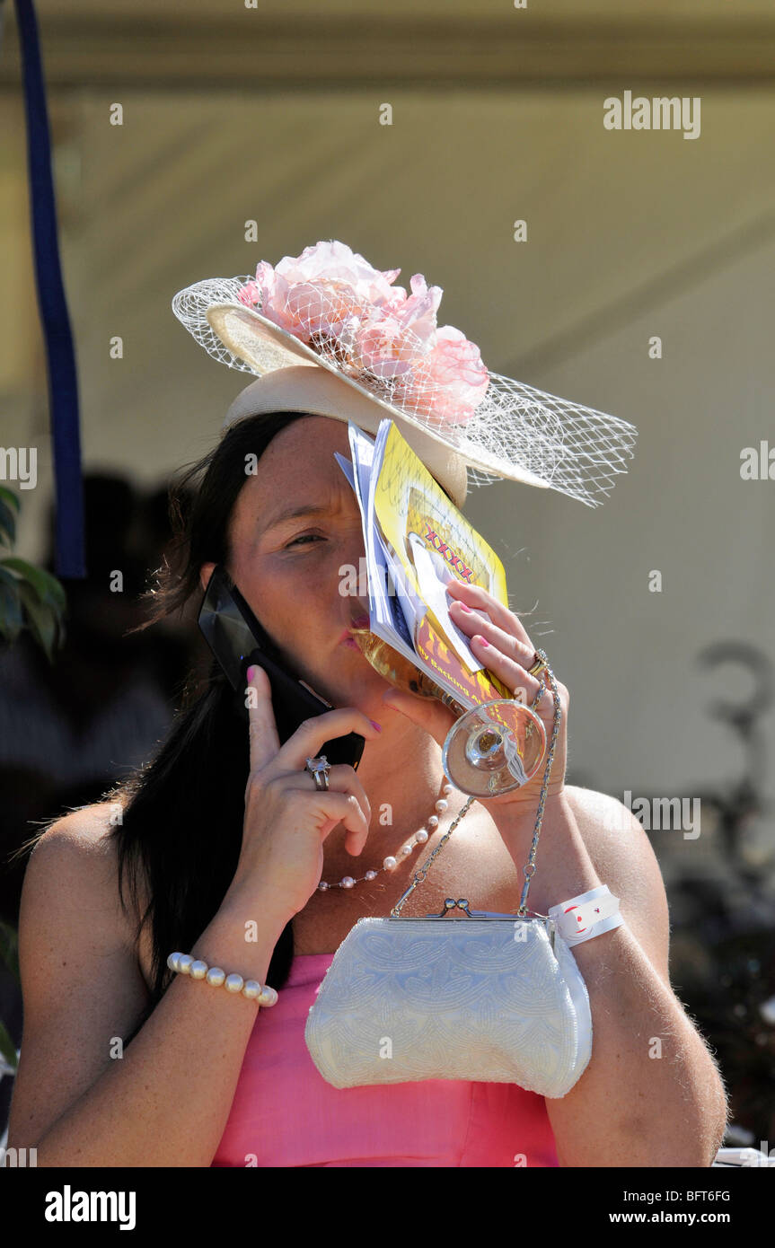 A race goer enjoys a sip of Champagne at the races at Pioneer Park race course in Alice Springs, Australia. - Stock Image