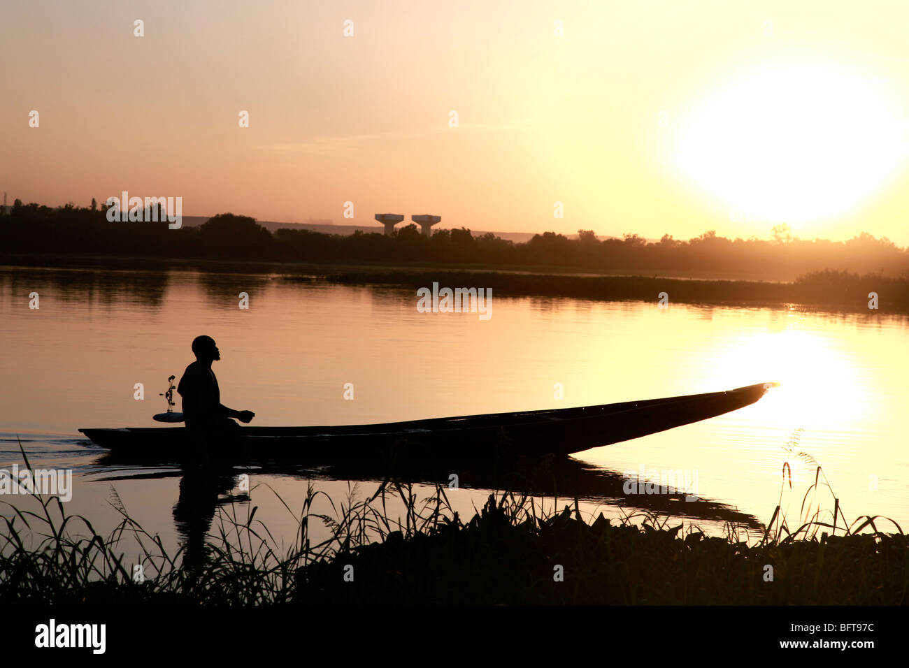 Fisherman in a small boot crossing a river at sunset - Stock Image