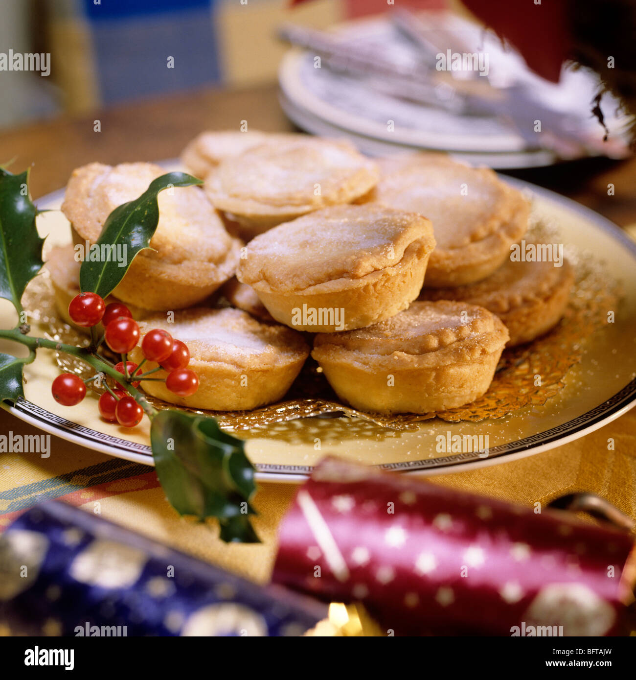 Plate of mince pies with sprig of holly decoration - Stock Image