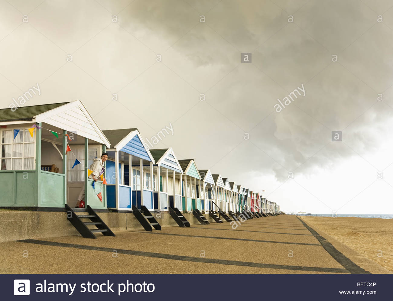 Taking shelter under Beach hut - Stock Image